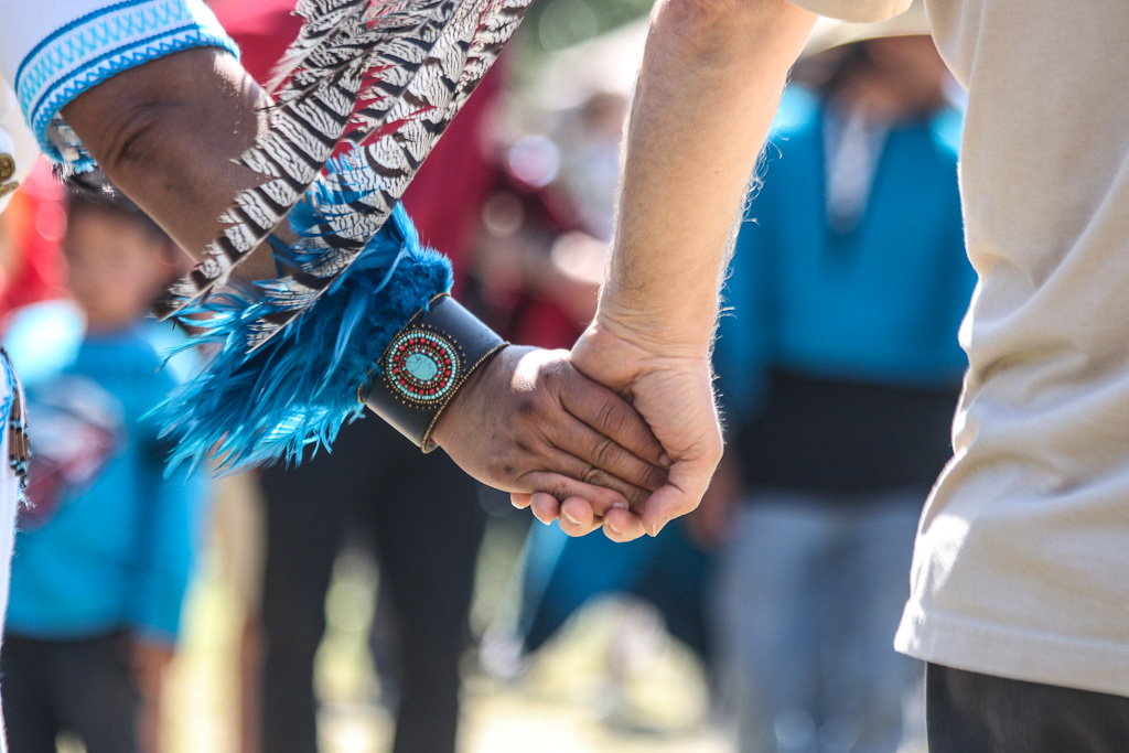 A Grupo Tlatelolco dancer and member of the audience hold hands on March 24 during Panhe as part of the circle dance in which everyone can join in.