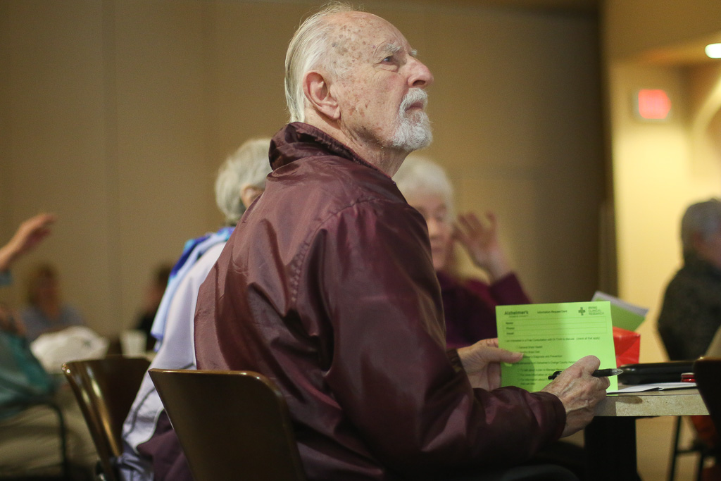 """Keith Leaburn, 86, listens to the presentation """"Medical Cannabis: Promoting Health without Creating Potheads"""" while holding an information card on Feb. 28 at the Dorothy Visser Senior Center in San Clemente. Photo: Eric Heinz"""