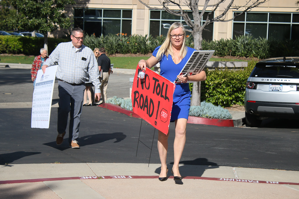 """San Clemente Assistant City Manager Erik Sund, left, and """"No Toll Road"""" activist Michelle Schumacher walk to the entrance of The Toll Roads headquarters on April 11 in Irvine. Photo: Eric Heinz"""