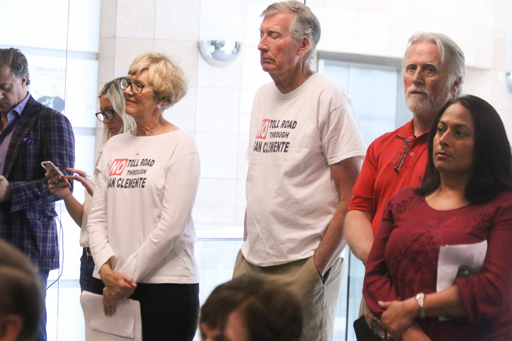 """People wearing """"No Toll Road Through San Clemente"""" T-shirts attend a TCA joint board meeting on April 11 in Irvine. Photo: Eric Heinz"""