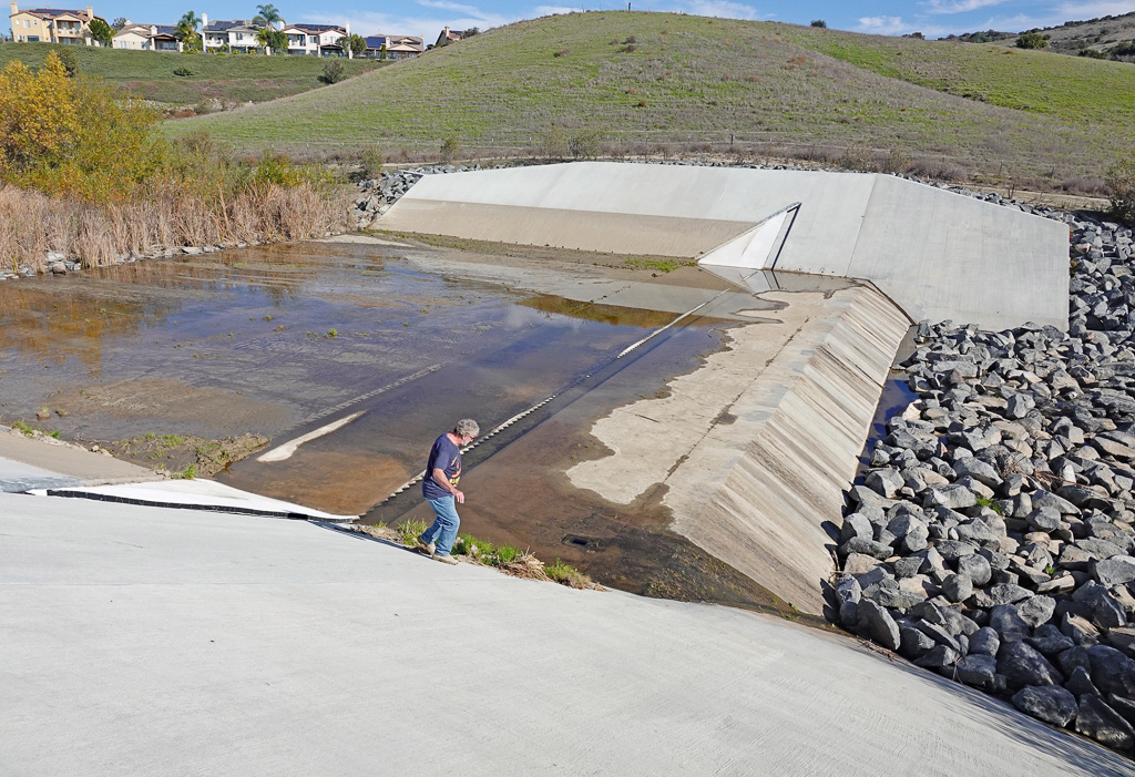 Roger Butow, environmental consultant on Santa Margarita Water District's 2015 Gobernadora retention basin project, examines an inflatable dam in its deflated state. Similar dams are being proposed in San Juan Capistrano. Photo: Fred Swegles