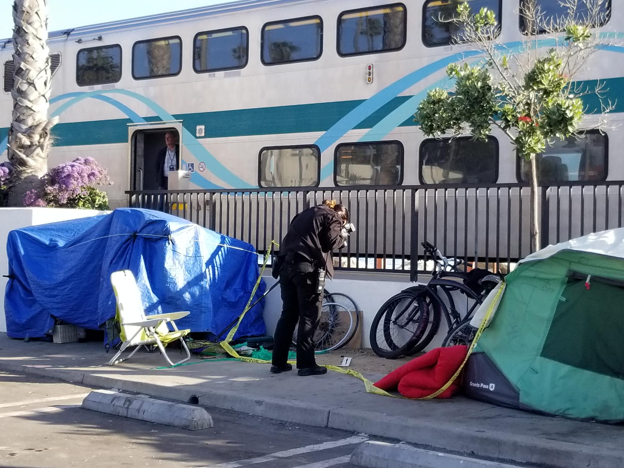 An OCSD Crime Scene Investigator photographs the scene of an alleged crime where a fight broke out between two homeless men. Photo: Cari Hachmann