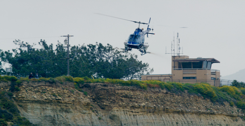A videographer who happened to be filming on April 19 at Lower Trestles captured this helicopter dropping VectorMax FG pellets near the beach trail and sands, according to Camp Pendleton officials who reviewed the video. Base officials said the substance is made with natural products and not harmful to humans, but surfers that day said they were unaware of the planned drop. Photo: Courtesy of Steve Kennedy