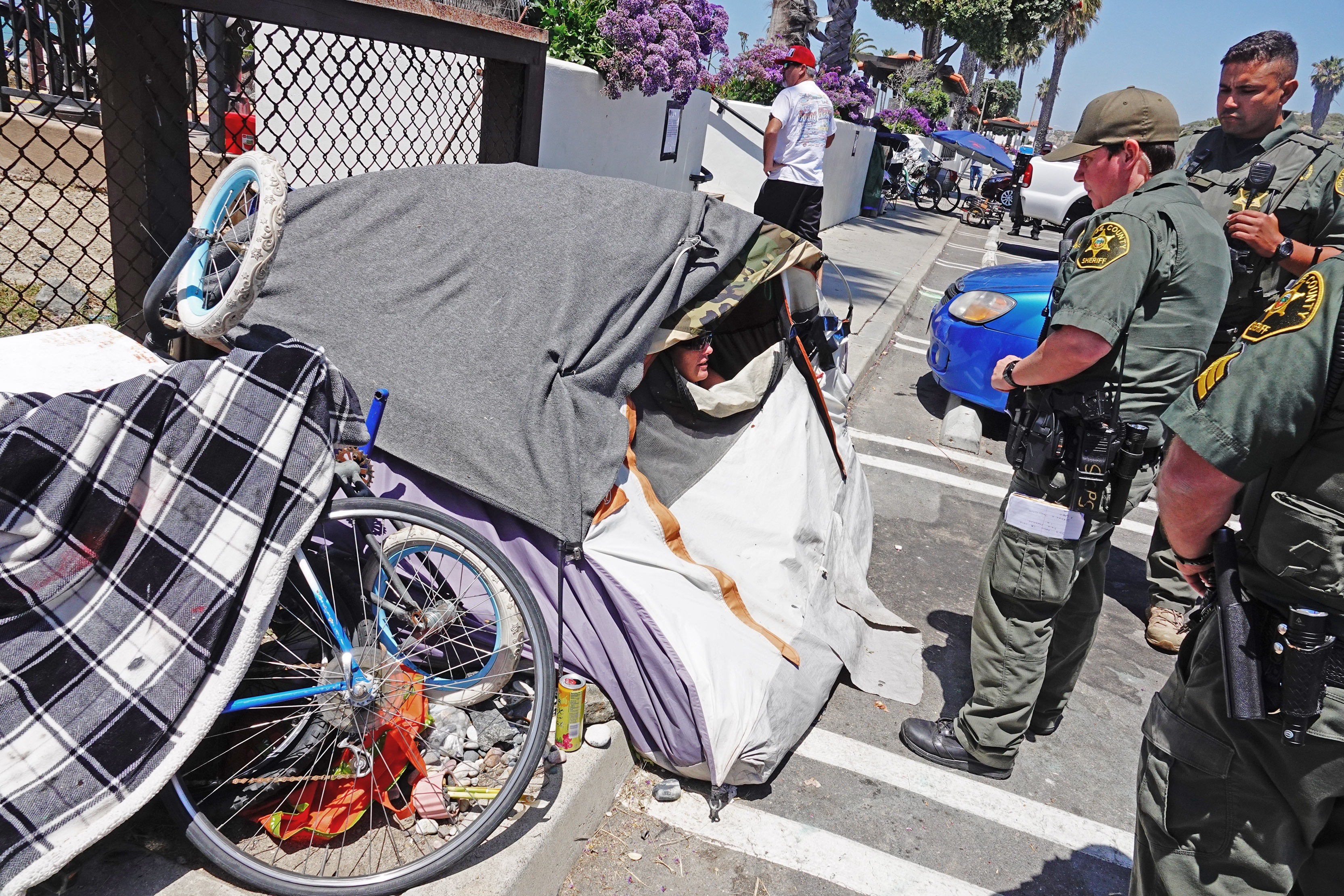 Sheriff's deputies at San Clemente's North Beach advise a camper on Friday, May 24. that she and her belongings must relocate. They offered her assistance to move to an area that the city of San Clemente has designated for homeless campers. Photo: Fred Swegles