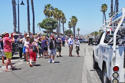 Bystanders who had turned out at San Clemente's North Beach on Friday, May 24, to witness the relocation of homeless campers applaud a city maintenance truck hauling belongings to a new, city-designated camping site. Photo: Fred Swegles