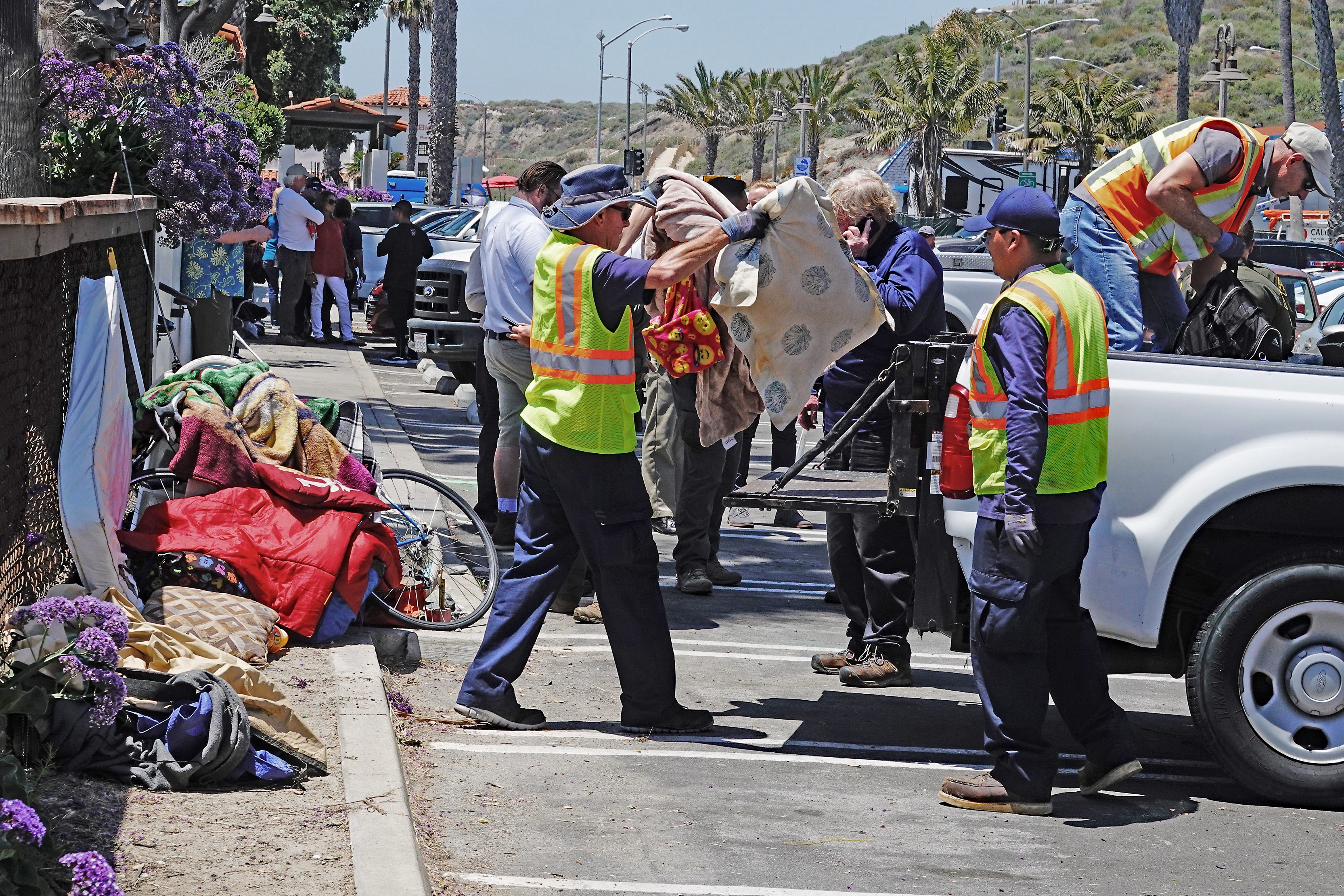 San Clemente city employees pack up a North Beach camper's belongings to haul them to a new designated camping area for homeless people on Friday, May 24. Photo: Fred Swegles