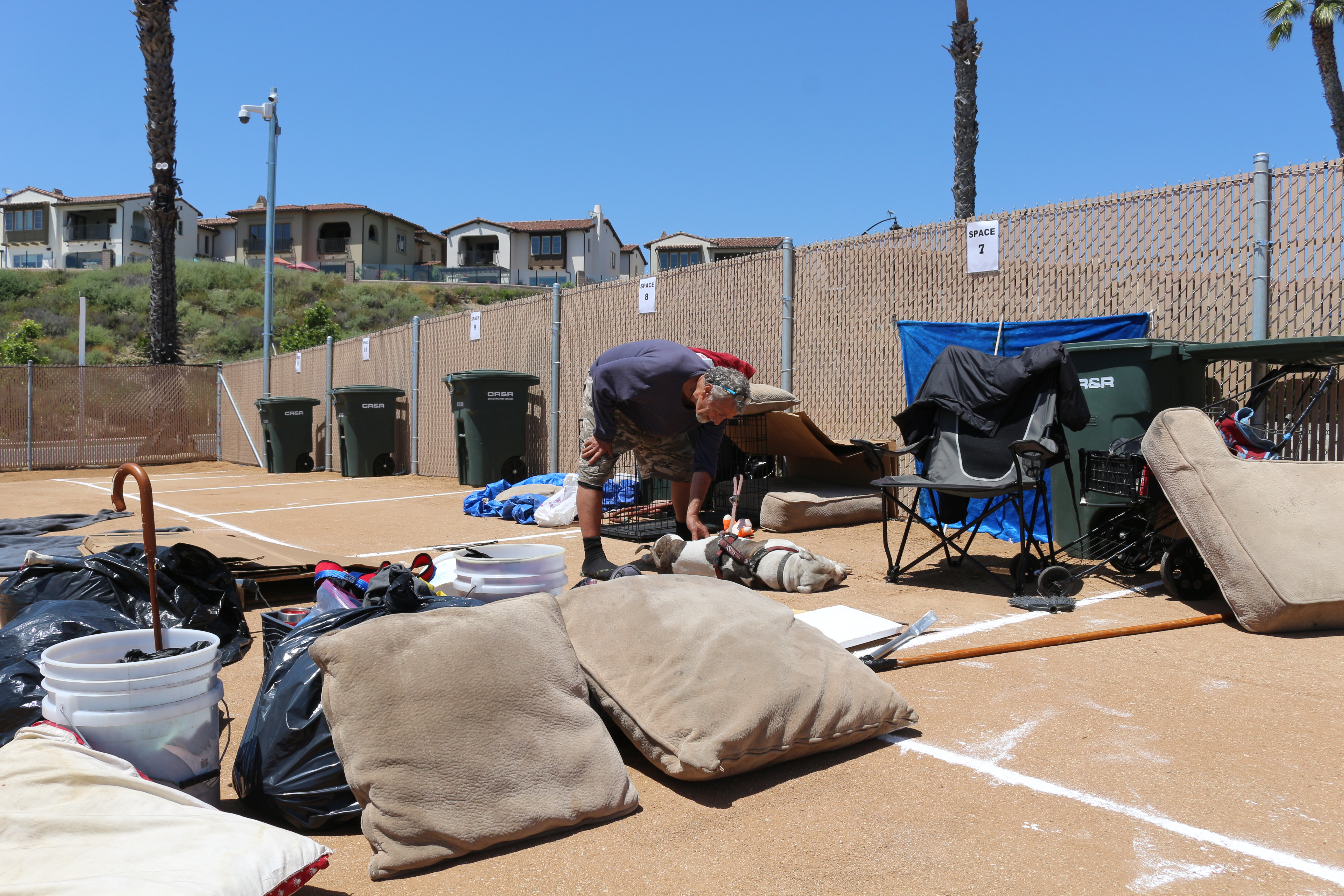 Steven Gustafson, 63, is one of the first to arrive at the city's designated lot for the homeless on Avenida Pico. Having just moved out of the North Beach parking lot, he works on setting up his campsite. Photo: Chelsie Rex