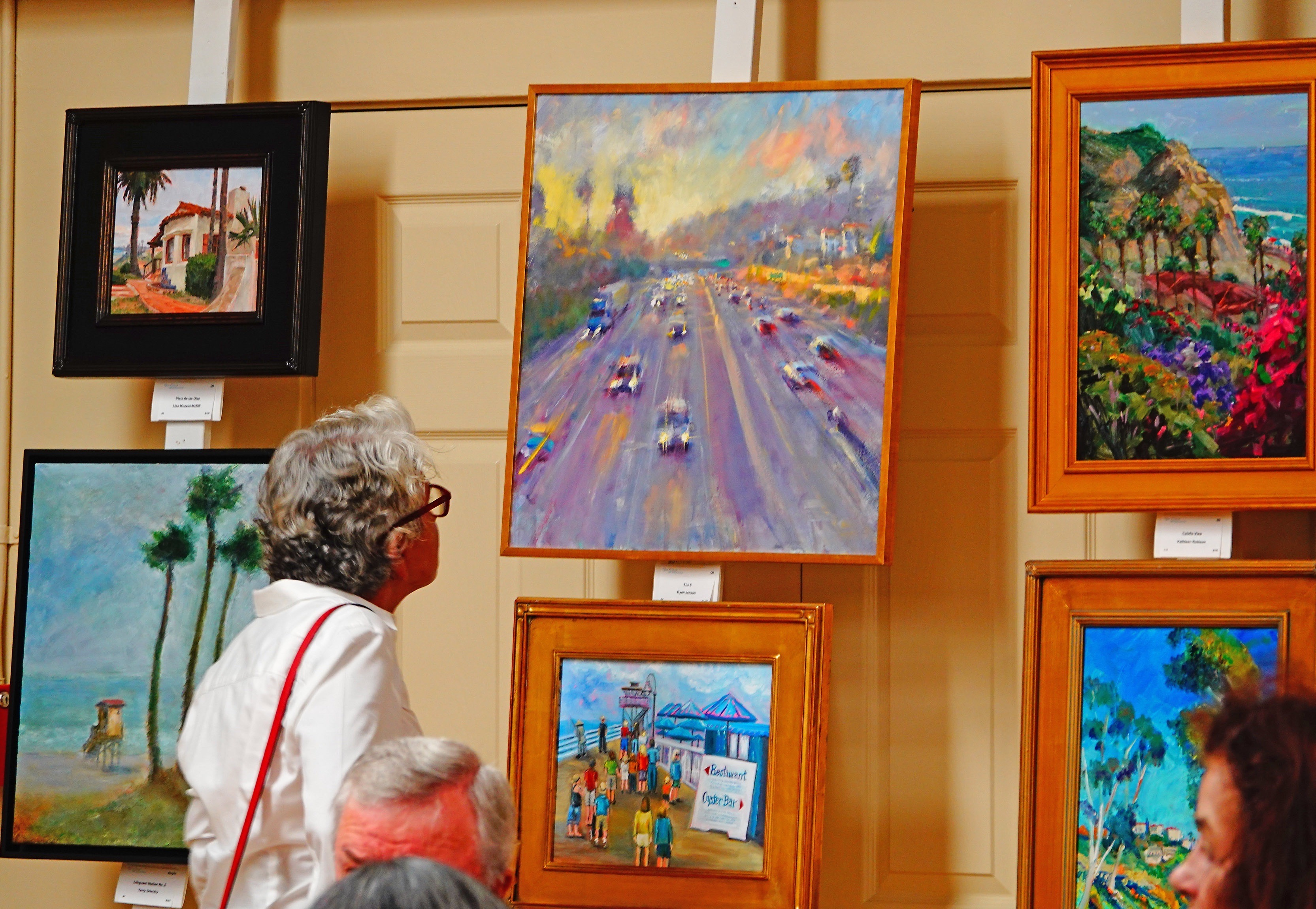 An attendee at this year's Paint San Clemente awards gala examines a few of the paintings vying for honors. Photo: Fred Swegles