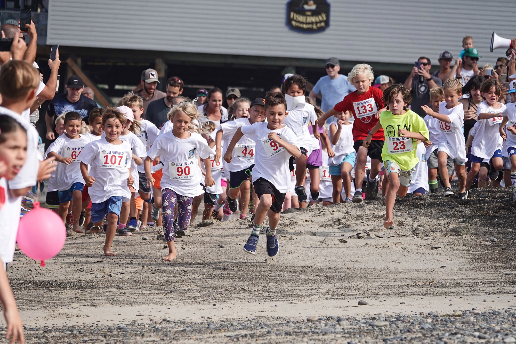 Feet go flying as children sprint from the starting line in the 2019 San Clemente Ocean  Festival Dolphin  Dash. Photo: Fred Swegles