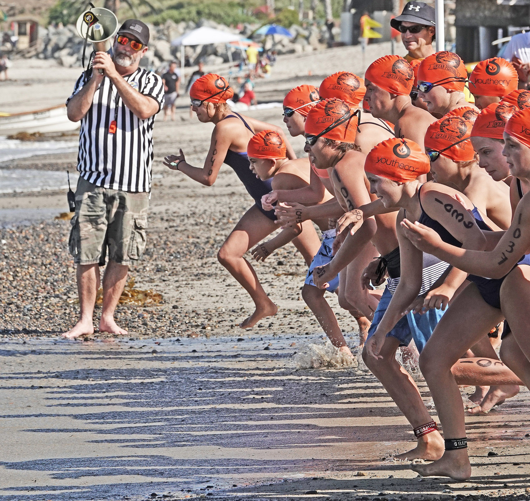 San Clemente junior lifeguards sprint for the water in their division of San Clemente Ocean Festival surf races. Photo: Fred Swegles