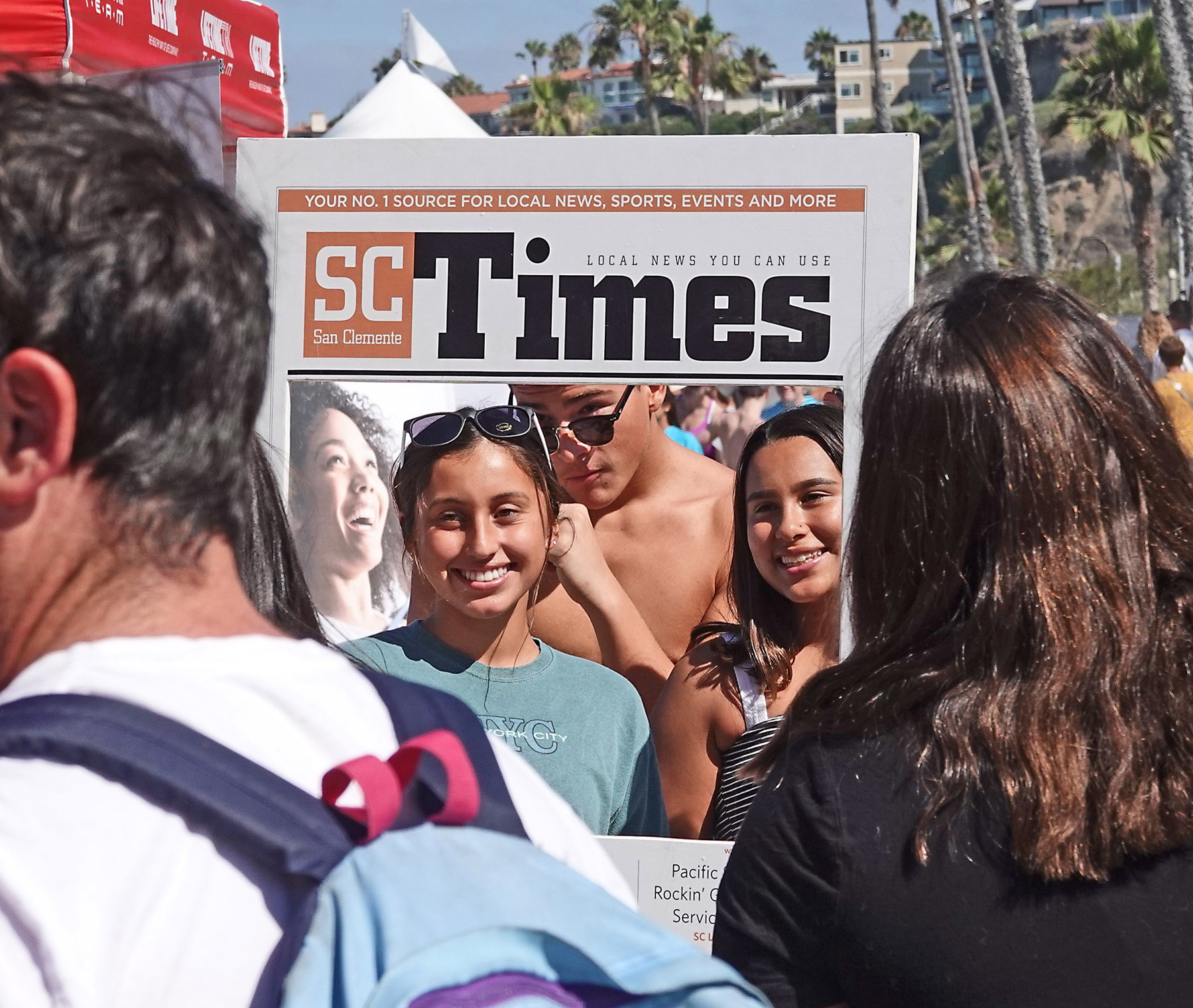 Serenity Ferris, Devin Baca and Lacey Rodriguez from Moreno Valley rode the beach train to the San Clemente Ocean Festival. They paused at the SC Times booth to have a friend photograph them as cover celebrities in the San Clemente Times. We have no idea who the person on the cover at left is. She was a face on a booth next door. Photo: Fred Swegles
