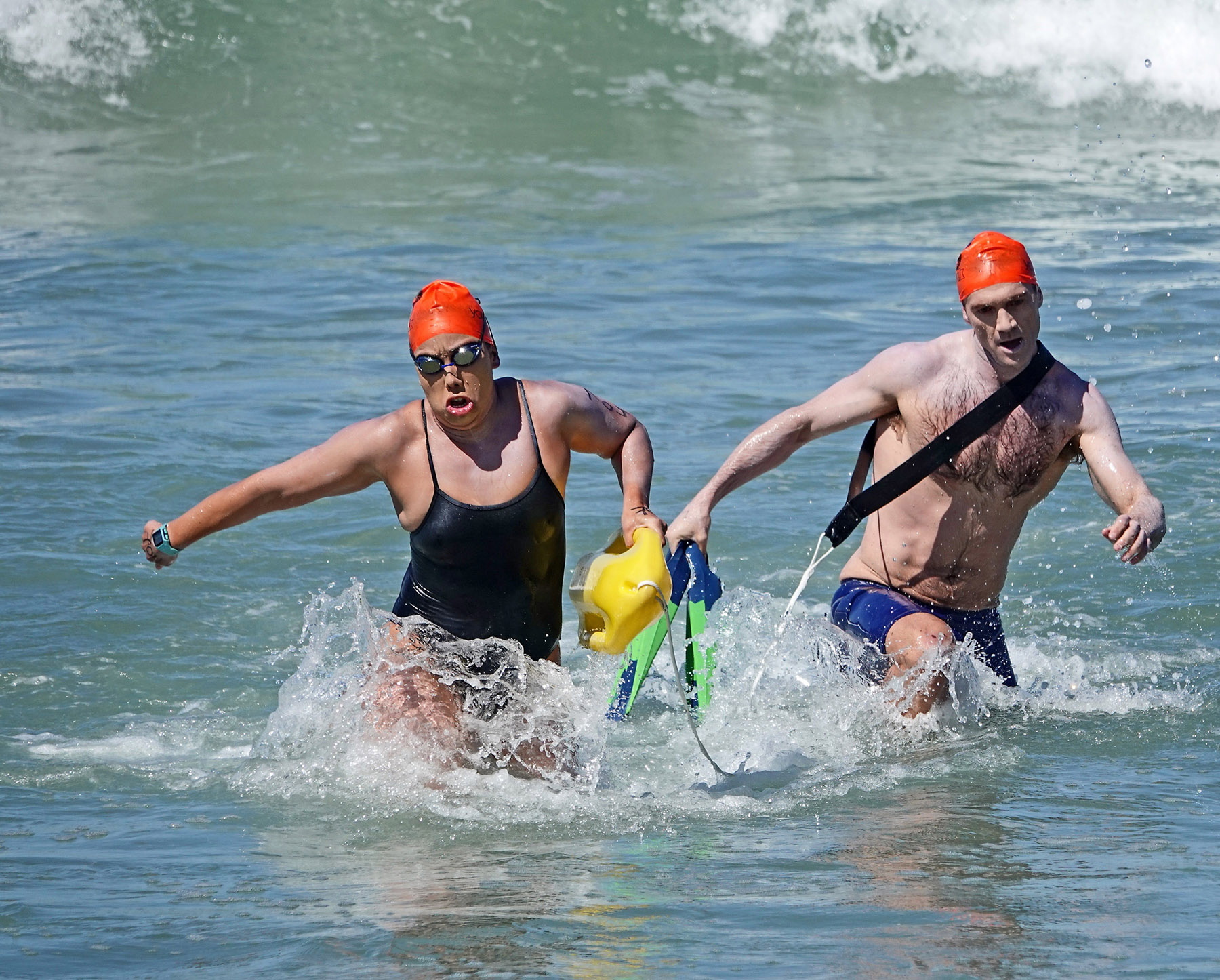 In a surf rescue relay race, 'victims' cooperate on the way in toward the finish line. Photo: Fred Swegles