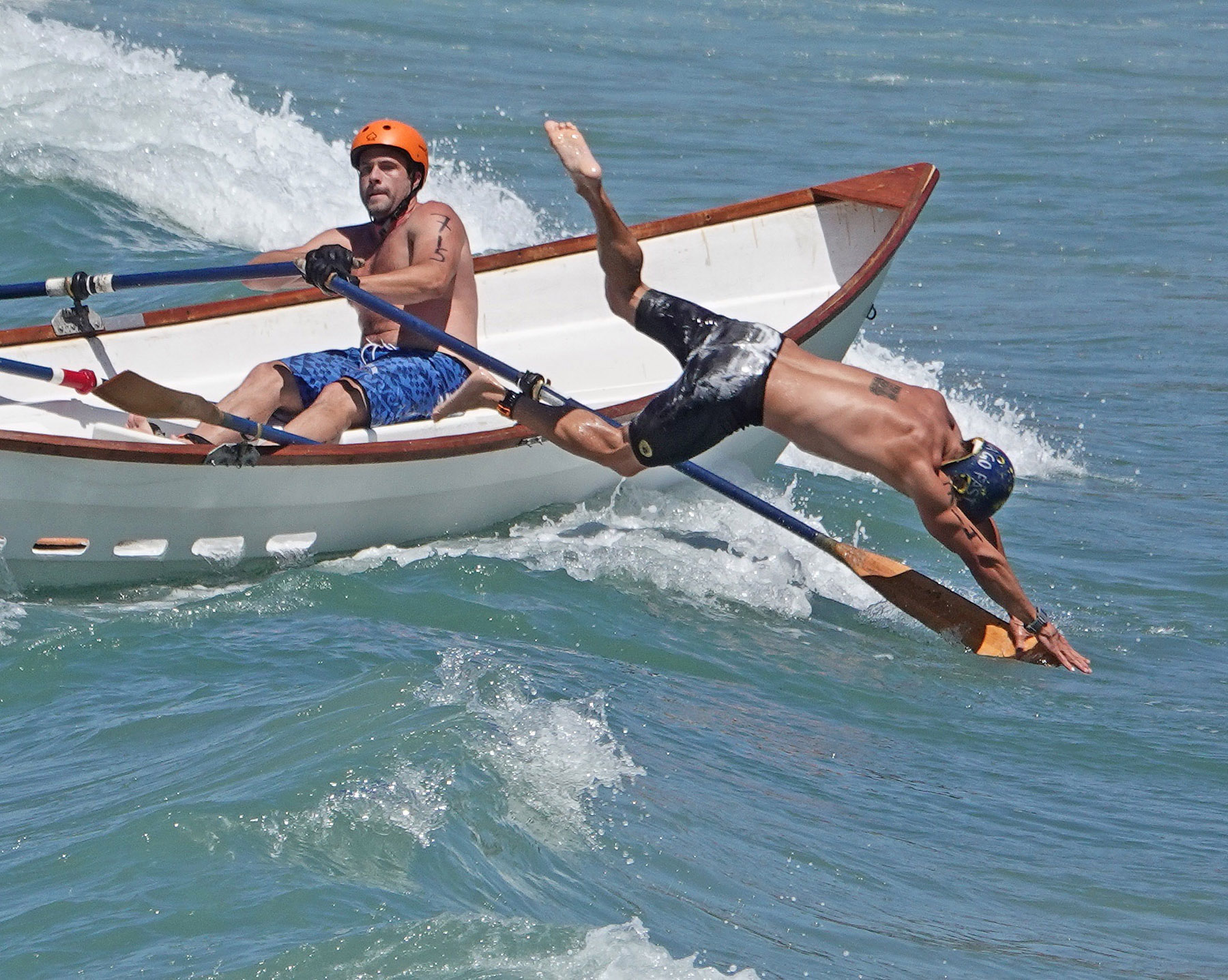 A doryman leaps forward to sprint onto shore and return to the boat swiftly so the team can row back out for the next lap of a race at the San Clemente Ocean Festival. Photo: Fred Swegles