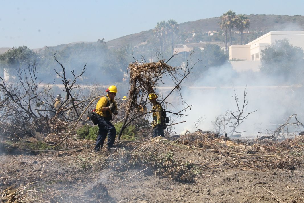 Orange County Fire Authority crews work to extinguish a brush fire on a hillside near Bella Collina golf course in San Clemente on Wednesday, July 24. Photos: Cari Hachmann