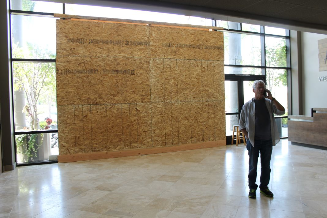 A church member stands in the lobby of Heritage Christian Fellowship where a car plowed through the church's main glass entrance, now boarded up. Photo: Cari Hachmann