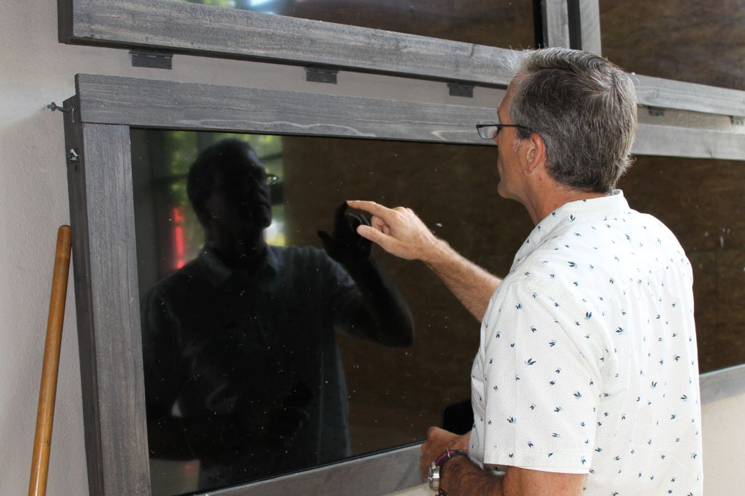 Roger Gales, senior pastor at Heritage Christian Fellowship, points to where glass shards were embedded into a fixture on the wall after a car plowed through the church's main entrance and sanctuary doors. Photo: Cari Hachmann